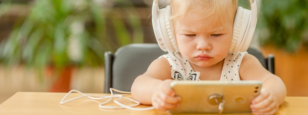 Baby with headphones and mobile phone