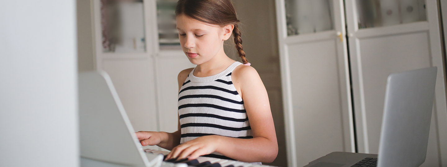 Girl at keyboard with laptop